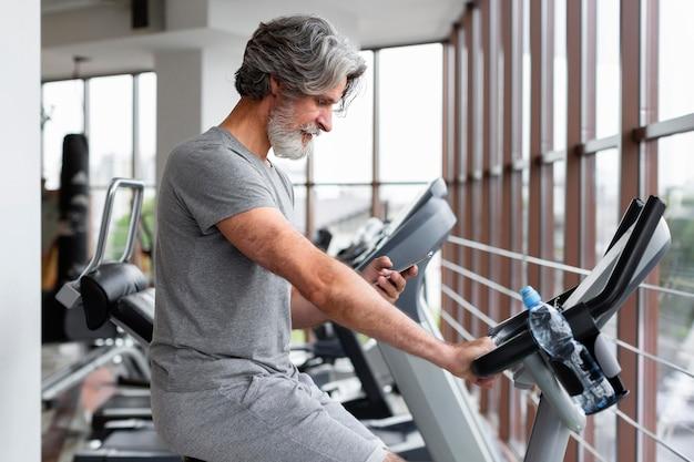 Seitenansichtsmann, der im fitnessstudio läuft
