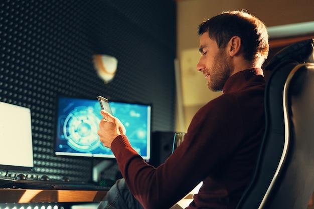 Seitenansichtsmann, der in einem ledersessel sitzt, der im studio mit einem smartphone und computern arbeitet. freiberufler hält handy arbeitet an filmmaterial, video, design. Premium Fotos
