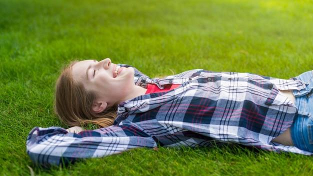 Seitenansichtsmileymädchen, das auf gras bleibt