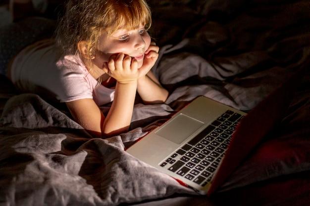 Seitenansichtsmileymädchen im bett mit laptop