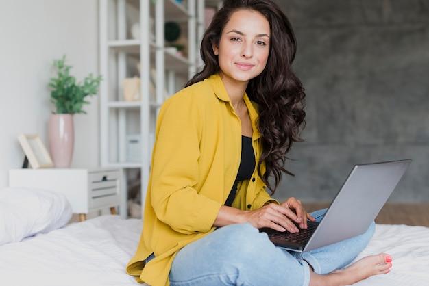 Seitenansichtsmileymädchen mit laptop zuhause