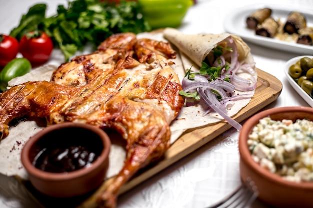 Seitenansichtstabak auf fladenbrot mit zwiebeln und soße mit salat und oliven