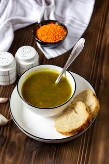 Seitenansichtsuppe mit linsen mit brotscheiben mit salz und pfeffer