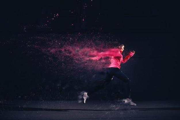Seitenbewegungsansicht des laufenden mädchens des sexy fitathleten in der sportbekleidung an der straße vor der grauen wand.