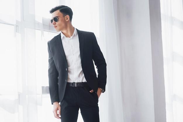 Seitenblick. porträt des jungen stilvollen mannes in der klassischen geschäftskleidung, die im weißen raum steht.