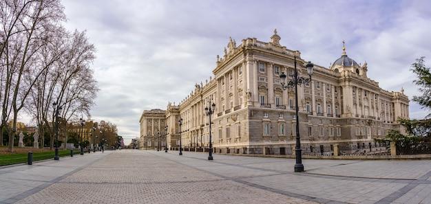 Seitenfassade des königlichen palastes von madrid, fußgängerzone mit laternenpfählen, bäumen und sonnigem tag mit wolken. spanien.
