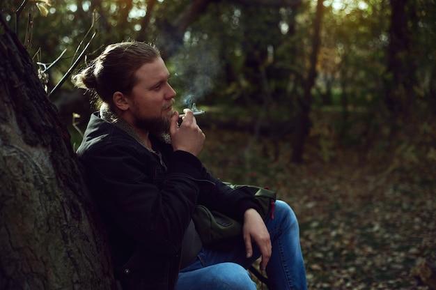 Seitenfoto eines rauchenden mannes im herbstwald. ein ruhender bärtiger wanderer. schlechte angewohnheiten