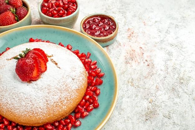 Seitennahaufnahme appetitlicher kuchenkuchen mit erdbeeren und granatapfel und die beerenschalen auf dem tisch