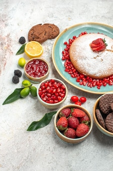 Seitennahaufnahme beeren und kekse der kuchen mit erdbeeren zitronenplätzchen zitrusfrüchte