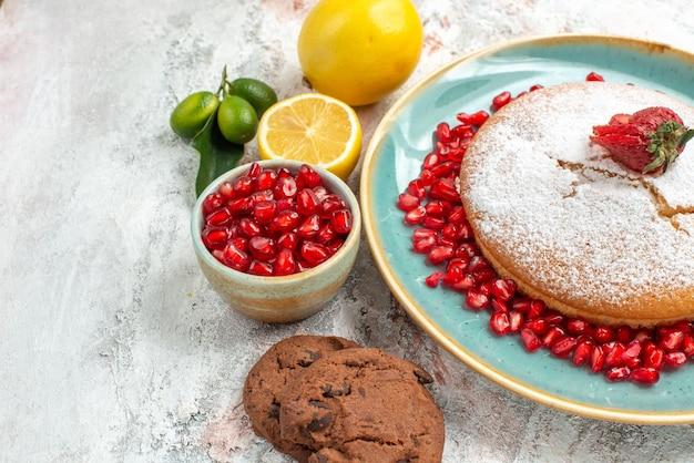 Seitennahaufnahme der kuchen zitrusfrüchte der kuchen mit erdbeerplätzchen granatapfel