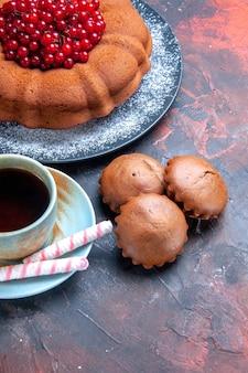 Seitennahaufnahme eine tasse tee ein kuchen mit roten johannisbeeren eine tasse tee süßigkeiten cupcakes