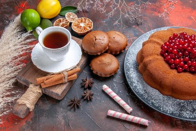 Seitennahaufnahme eine tasse tee ein kuchen mit roten johannisbeeren sternanis eine tasse tee auf dem brett