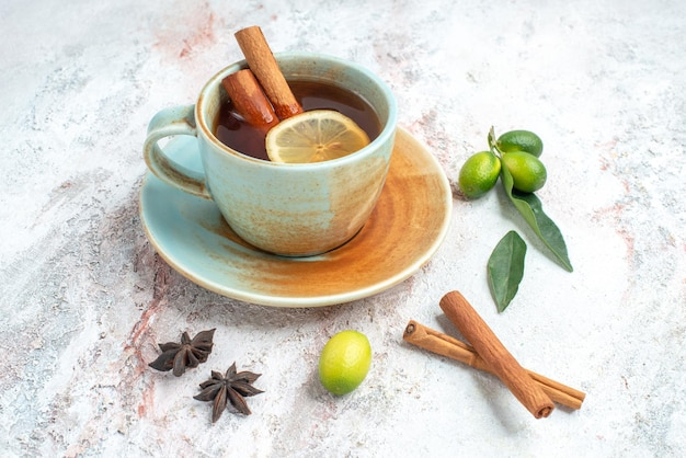 Seitennahaufnahme eine tasse tee eine tasse tee mit zitrone und zimt auf der untertasse mit zitrusfrüchten sternanis und zimtstangen auf dem tisch