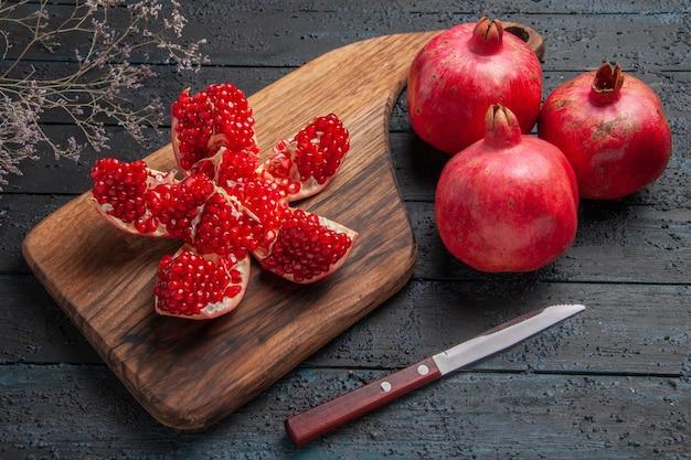 Seitennahaufnahme granatäpfelmesserbrett reif gepillter granatapfel auf schneidebrett neben drei roten granatapfelmessern und ästen auf dunklem hintergrund