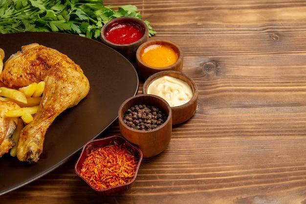 Seitennahaufnahme hähnchenteller mit hühnchen pommes frites neben den kräuterschalen mit verschiedenen saucen und gewürzen