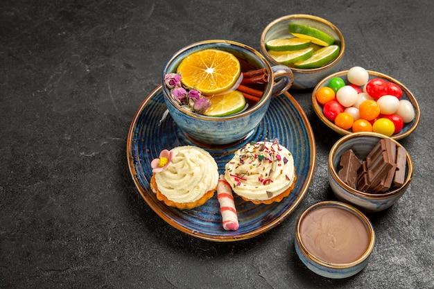 Seitennahaufnahme kräutertee eine tasse tee mit zitrone und cupcakes mit sahne neben den schalen mit schokoladenscheiben aus limetten-schokoladencreme und bunten süßigkeiten auf dem tisch