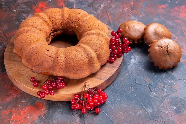 Seitennahaufnahme kuchen cupcakes drei cupcakes ein kuchen mit roten johannisbeeren auf dem brett