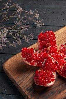 Seitennahaufnahme pilled granatapfel und äste pilled granatapfel auf küchenbrett neben ästen auf dunklem hintergrund
