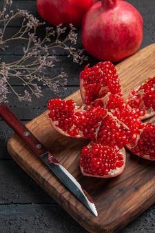 Seitennahaufnahme pilled granatapfel und äste pilled granatapfel auf küchenbrett neben baum äste messer und zwei granatäpfel auf dunklem hintergrund