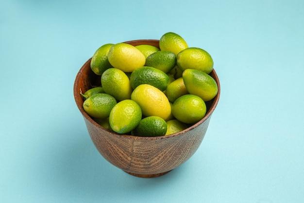 Seitennahaufnahmefruchtschale mit grünen früchten auf der blauen oberfläche