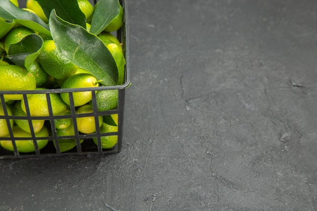 Seitennahaufnahmefrüchte dunkler obstkorb mit blättern auf dem dunklen tisch