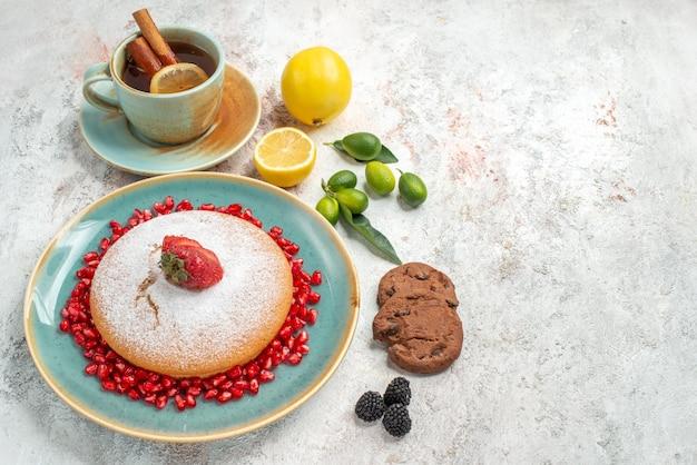 Seitennahaufnahmekuchen der appetitliche kuchen mit granatapfel-zitrusfruchtkeksen auf dem tisch