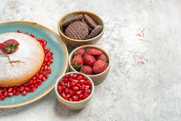 Seitennahaufnahmekuchen ein appetitlicher kuchen erdbeeren granatapfel-schokoladenkekse in schalen