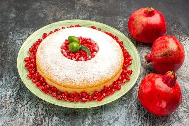 Seitennahaufnahmekuchen mit granatäpfeln drei granatäpfel und der teller eines appetitlichen kuchens