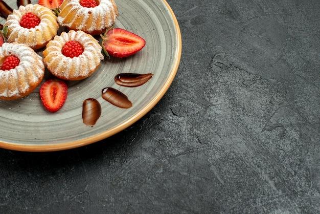 Seitennahaufnahmeplätzchen in tellerplätzchen mit erdbeere und schokolade auf weißem teller auf der linken seite des schwarzen tisches