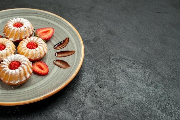 Seitennahaufnahmeplätzchen in tellerplätzchen mit schokolade und erdbeere auf weißem teller auf der linken seite des schwarzen tisches