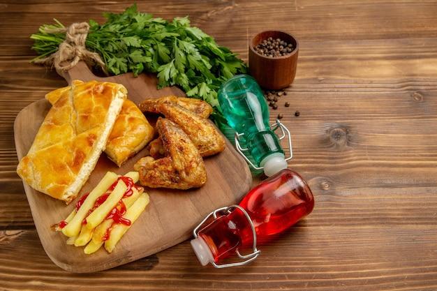 Seitennahaufnahmeschale auf dem brett fastfood auf dem brett neben der schüssel mit schwarzen pfefferkräutern und roten und blauen flaschen
