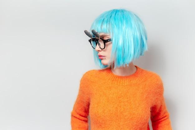 Seitenporträt der jungen frau mit blauer bob-frisur, orangefarbenem pullover und sonnenbrille tragend.