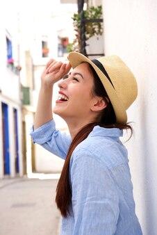 Seitenporträt der lachenden frau stehend in der straße mit der hand zum hut