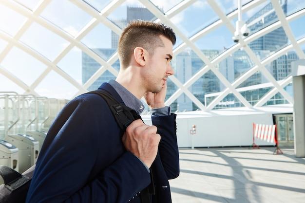 Seitenporträt des ernsten mannes beim handyanruf mit rucksack