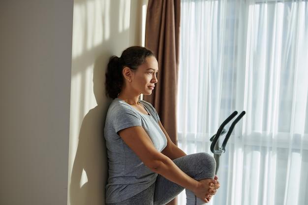 Seitenporträt einer jungen sportlichen brünetten frau, die ihren rücken gegen eine wand lehnt und die muskeln streckt
