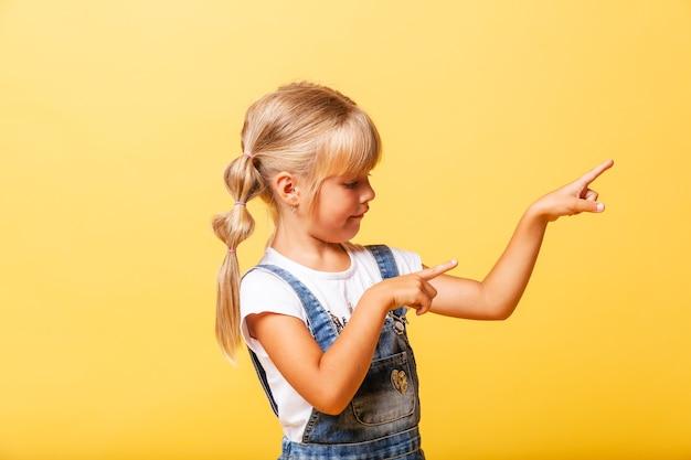 Seitenporträt eines kleinen mädchens. sie ist süßes süßes attraktives fröhliches blondes mädchen, das zeigt