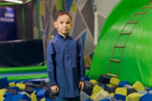 Seitenporträt eines kleinen muslimischen jungen, der einen hijab trägt. konzept der muslimischen kleidung für kinder. vor dem hintergrund des spielplatzes.