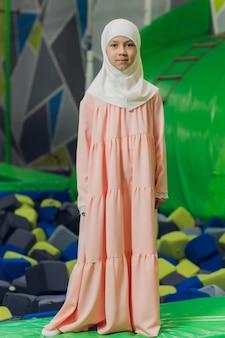 Seitenporträt eines kleinen muslimischen mädchens, das einen hijab trägt. konzept der muslimischen kleidung für kinder. vor dem hintergrund des spielplatzes.