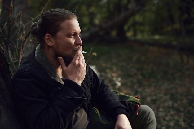 Seitenporträt eines rauchenden jungen bärtigen abenteurers, der sich im herbstwald entspannt