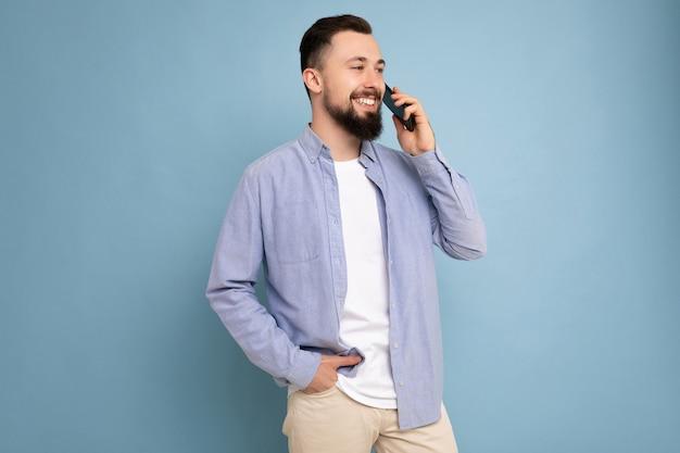 Seitenprofil fotoaufnahme eines gut aussehenden jungen, brünetten, bärtigen mannes, der ein lässiges blaues hemd und ein weißes t-shirt trägt, das isoliert auf blauem hintergrund mit leerem raum in der hand gehalten und kommuniziert wird