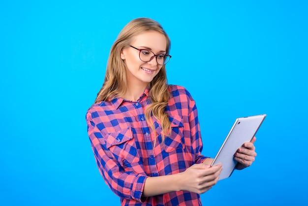 Seitenprofil halbgedrehtes porträt von fröhlicher, süßer, süßer, charmanter schöner art mit langem blondem haarmanager, der informationsnachrichten auf dem pad einzeln auf blauem hintergrund überprüft