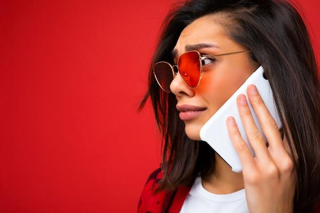 Seitenprofil-nahaufnahmefoto einer attraktiven, traurigen jungen brunet-frau, die ein stylisches rotes hemd weiß trägt