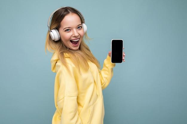 Seitenprofil schöne positive junge blonde frau mit gelbem stylischem hoodie isoliert auf blau