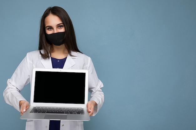 Seitenprofilaufnahme der jungen brunetfrau, die medizinischen weißen mantel und schwarze maske hält, die laptop hält und kamera lokalisiert auf blauer wand betrachtet