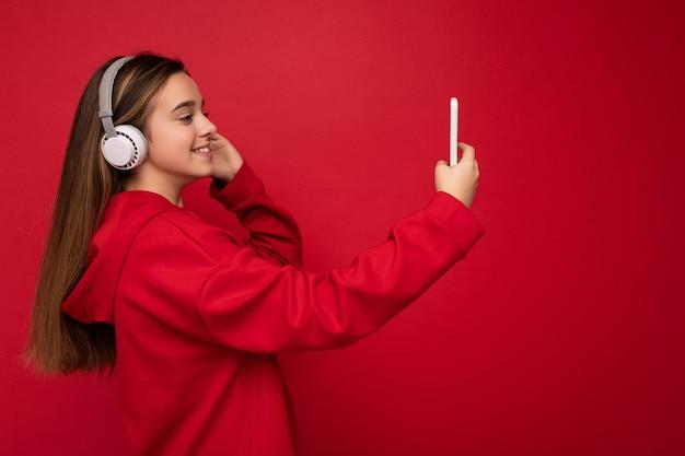 Seitenprofilaufnahme des glücklichen lächelnden hübschen brünetten mädchens, das roten kapuzenpulli auf rotem hintergrund trägt