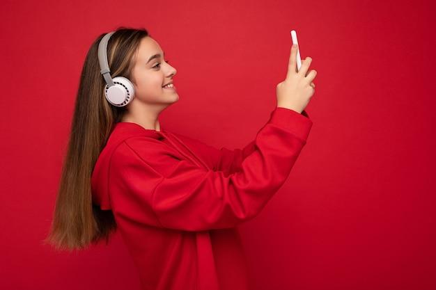 Seitenprofilaufnahme eines glücklich lächelnden hübschen brünetten mädchens, das einen roten hoodie auf rotem hintergrund trägt