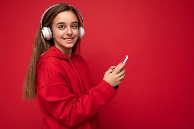 Seitenprofilaufnahme eines positiv lächelnden hübschen brünetten mädchens mit rotem hoodie isoliert auf rot