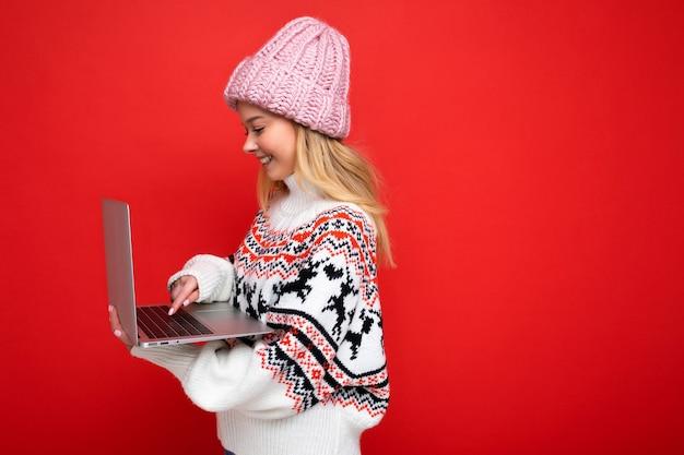 Seitenprofilfoto der charmanten hübschen jungen dame, die laptop isoliert über der wandhintergrundeingabe hält