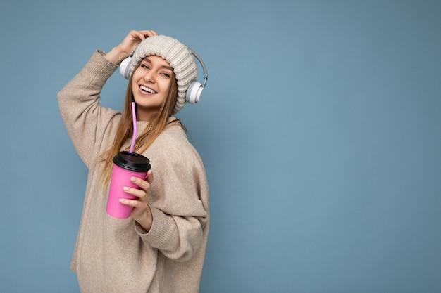 Seitenprofilfoto der schönen glücklich lächelnden jungen blonden frau, die beige winterpullover und -hut trägt