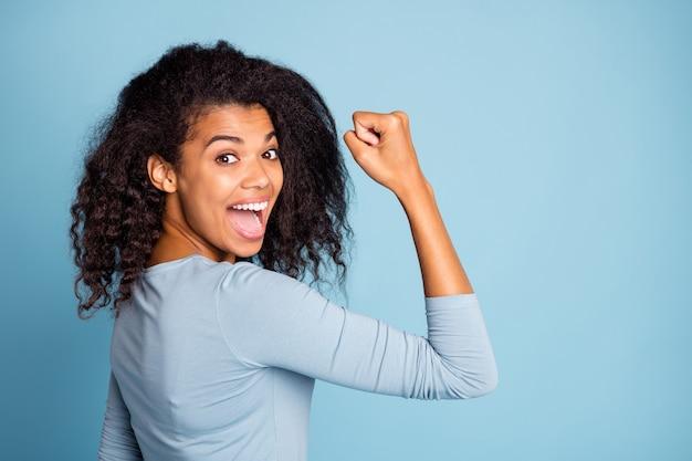 Seitenprofilfoto des fröhlichen aufgeregten niedlichen netten netten hübschen mädchenhaften weiblichen jungen, der stärke in ihren muskeln nach jahren des trainings zeigt, isolierte blauen pastellfarbenhintergrund